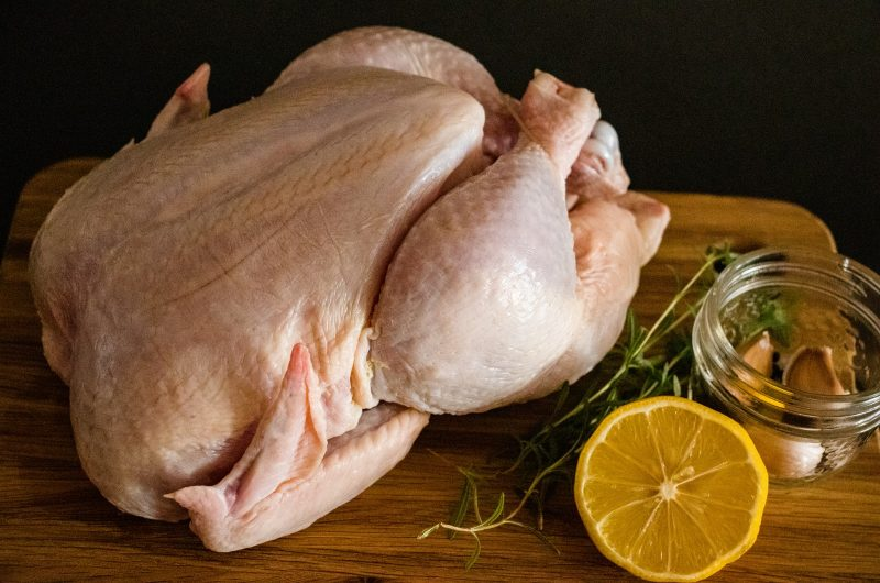 raw chicken meat on brown wooden chopping board